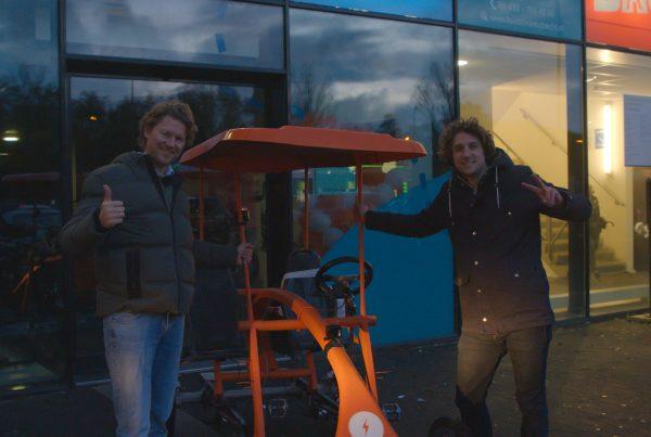 Alexander Stolze en Tijs Koedam bij de oranje Op De Fiets Met fiets pratend over vitaliteitsmanagement en wellbeing